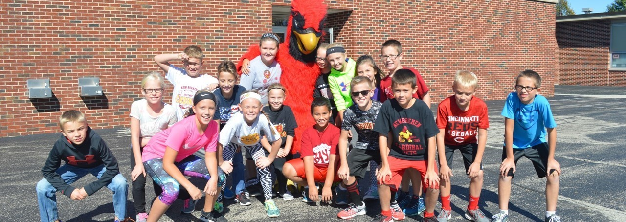 students on playground with Cardinal Mascot